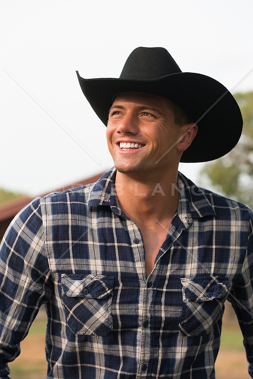 good looking  cowboy in a plaid shirt smiling