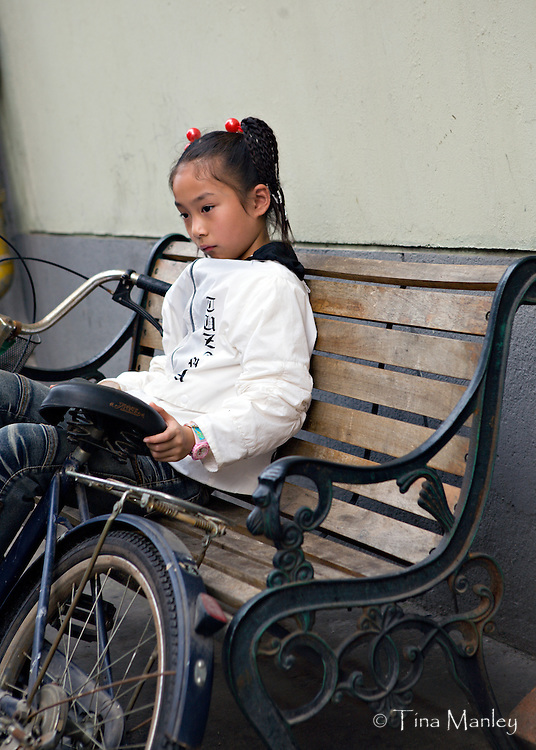 CHINA, HANGZHOU:  Cute young Chinese girl rests with her bicycle on a wooden bench in the marketplace of Hangzhou.