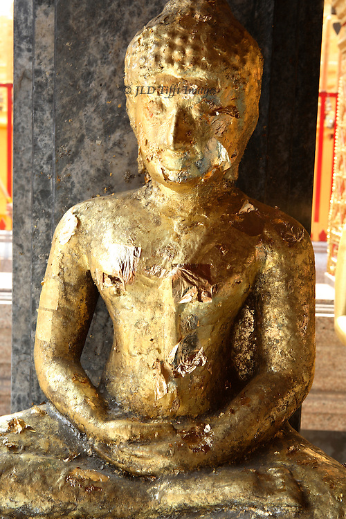 Chiang Mai, Wat Phrathat Doi Suthep, Buddha statue, seated, covered with gold leaf peeling slightly.