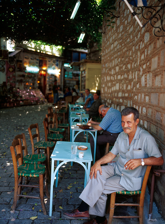 Man smokes a cigarette in street side cafe under a canopy of grape vines in the town of Agiassos on Lesvos, Greece