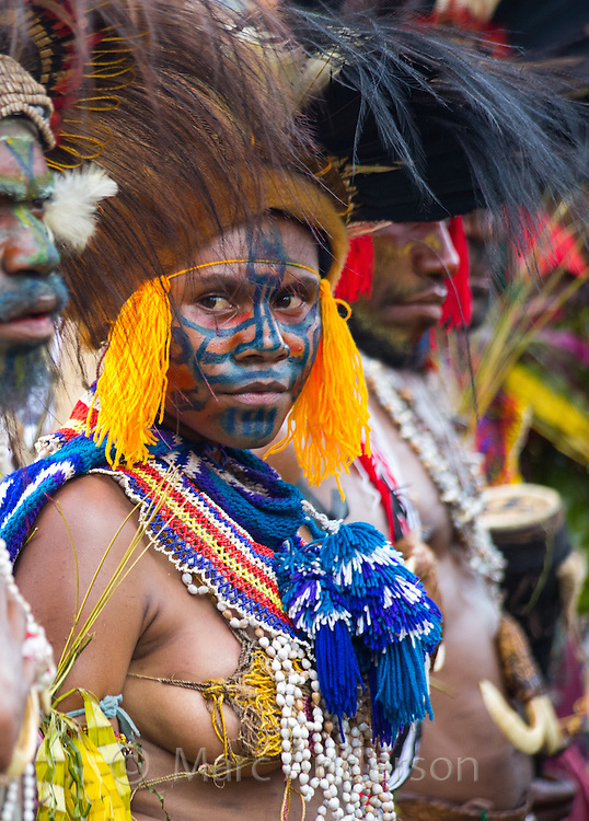Woman standing in a group wearing traditional tribal dress for the Goroka Show, an annual Singsing Festival in the highlands of Papua New Guinea. She is wearing colourful cotton necklaces, a headdress and her face is painted with blue patterns.