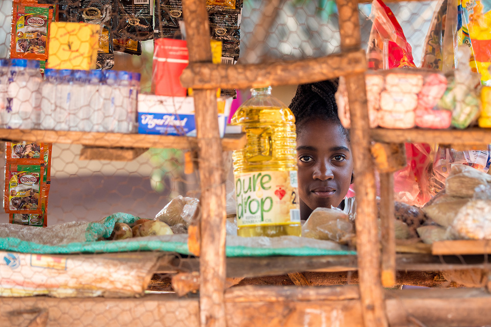 Zambian woman peers through small window in grocery store, Mukuni Village, Zambia