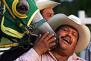 "Adolfo Chavero hugs his horse ""El Jugete"" after winning his race Saturday. Chavero runs a race track in Swansea, one of many popping up in South Carolina as the Hispanic population increases."