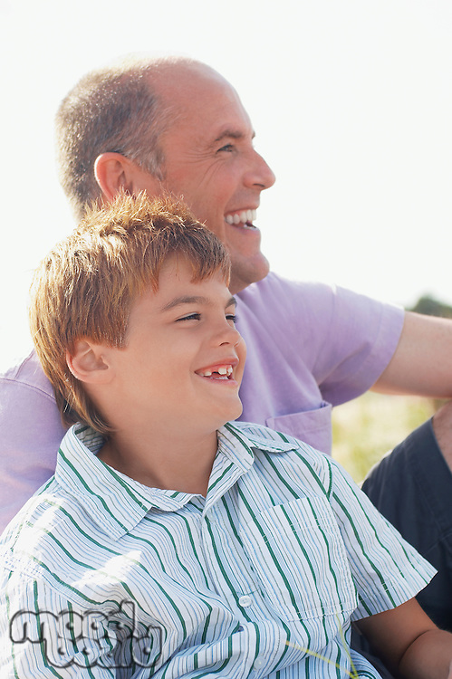 Father and Son sitting on beach looking at view portrait