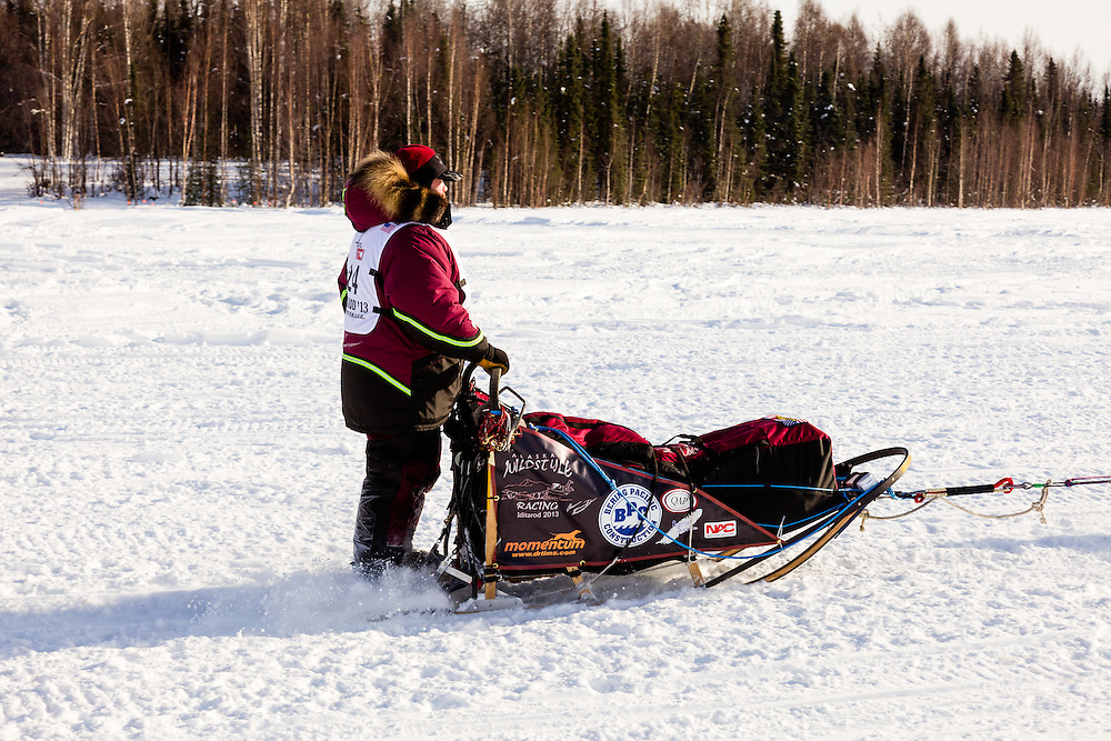 Musher Aaron Burmeister competing in the 41st Iditarod Trail Sled Dog Race on Long Lake after leaving the Willow Lake area at the restart in Southcentral Alaska.  Afternoon.