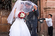 03 APRIL 2004 - SAN MIGUEL DE ALLENDE, GUANAJUATO, MEXICO: The bride and groom are pelted with rice as they come out of the church after their wedding at the Iglesia Parroguia, the principal Catholic church in San Miguel de Allende, Mexico. San Miguel, which was founded in the 1600s, is one of Mexico's premier colonial cities. It has very strict zoning and building codes meant to preserve the historic nature of the city center. About 7,500 US citizens, mostly retirees, live in San Miguel. PHOTO BY JACK KURTZ