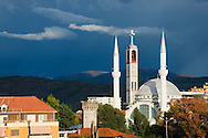 The tower of Shkodër Cathedral, also known as St Stephen's Catholic Cathedral, framed by two minarets of a neighborhing mosque, in Shkodër, Albania