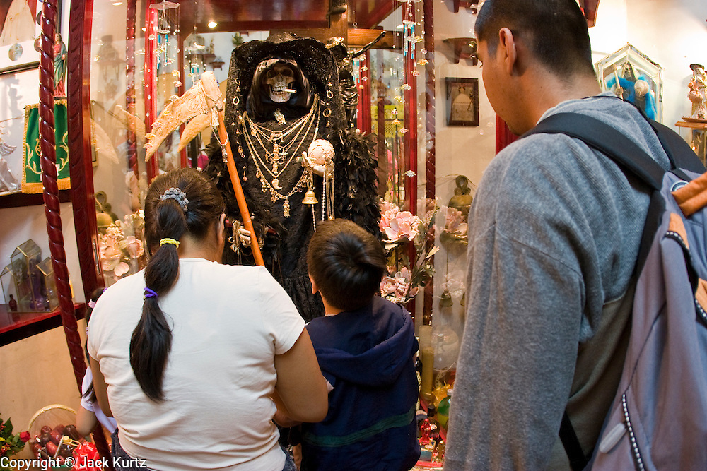 05 NOVEMBER 2004 - MEXICO CITY, MEXICO: Mexican families pray to Santa Muerte (St. Death) in Iglesia de la Piedad (Mercy Church) in the Tepito section of Mexico City. St. Death is venerated throughout Mexico and Mexican communities in the United States. The veneration of St. Death started in Mexico's prisons about 10 years and has since spread through working class neighborhoods in many Mexican cities. The worship St. Death was recognized as an official by the Mexican government in 2003. The Catholic Church in Mexico is opposed to the worship of St. Death and has held rallies and prayer vigils against the Saint. The small church in Tepito is frequently swamped with visitors and the religion has spread quickly through the tough, drug and crime plagued neighborhood, widely considered the most lawless in Mexico City.  PHOTO BY JACK KURTZ