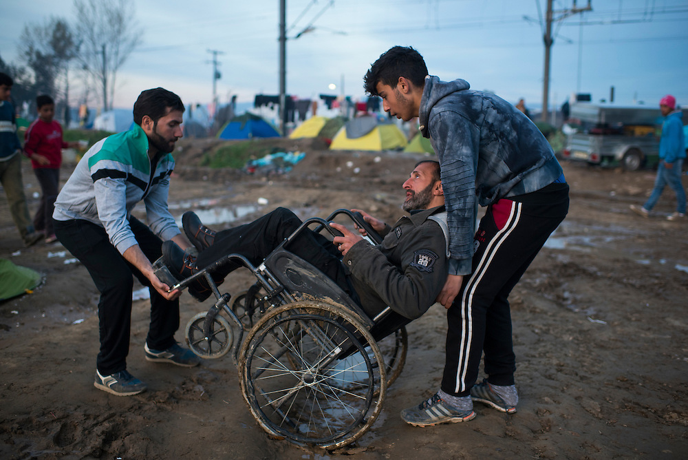 Refugees carry a man in a wheelchair across a muddy expanse at a camp on the Macedonian (FYROM) border on March 8, 2016 in Idomeni, Greece.