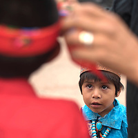 Eric Sclecion watches his father Dion Sclecion tie a head scarf on Celvon Shebola Thursday in Zuni before the night parade.