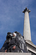 A Sikh man stands under one of the four lions at the base of Nelson's Column in London's Trafalgar Square.