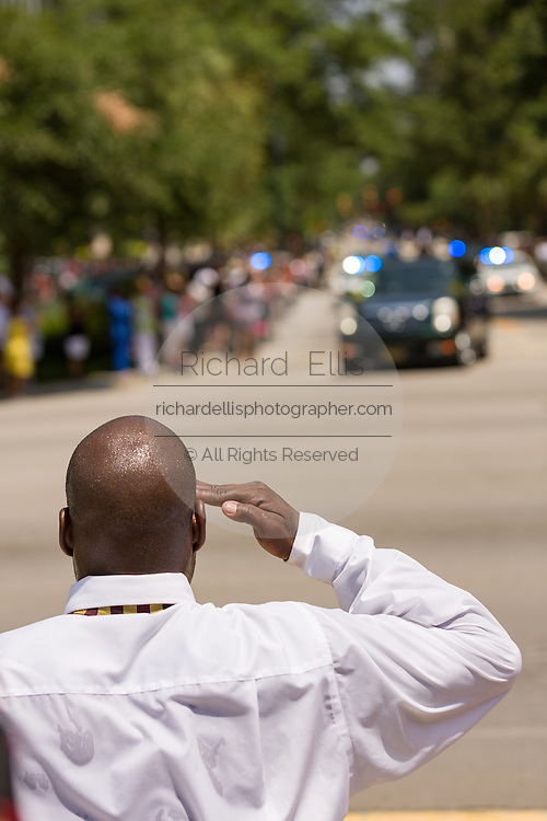 A mourner salutes as the horse-drawn caisson carrying the casket of slain State Senator Clementa Pinckney arrives at the State House June 24, 2015 in Columbia, South Carolina. Pinckney is one of the nine people killed in last weeks Charleston church massacre.