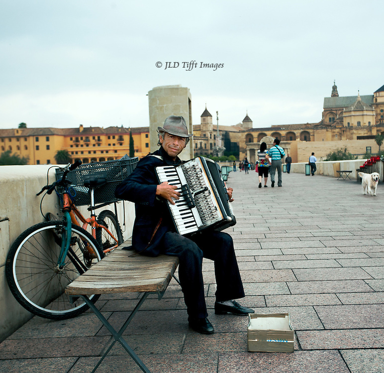 Gypsy male accordionist seated on a bench on the Roman bridge into Cordoba, Spain.  His bicycle leans against the wall. He plays his instrument for the camera, smiling.