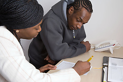 Receptionist filling out an appointment card for an offender on probation,