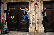 Three Parisians gain an advantage by climbing higher than pavement level to watch the patriotic Bastille Day Procession from a doorway on the Avenue Champs-Élysées, Paris. The young men have lodged themselves awkwardly a metre above the ground, resting their feet on various door catches and ledges, as if floating in mid-air. On a street traffic sign the French words 'Defense de Stationner' are written which in English translates as 'No Stopping', referring to vehicles not pedestrians. There is graffiti tagging sprayed on the walls and a brown stain at the bottom of a drainpipe