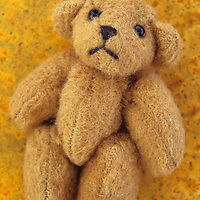 Small pale brown teddy bear with chunky arms and legs and sad expression lying on rusty metal sheet