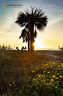 Couple silhouetted by the sunset ast Blind Pass Beach on Sanibel Island, Florida, USA