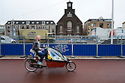 Een man fietst met twee kinderen in de bakfiets langs de bouwplaats voor de aanleg van de Catherijnesingel in Utrecht.<br />