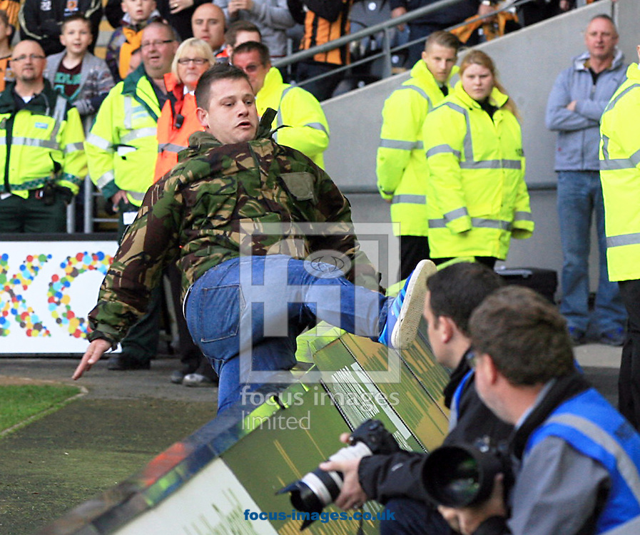 A fan is chased off the field as steward look on but then slips as he trys to jumps the advertising boards during the Barclays Premier League match at KC Stadium, Hull<br /> Picture by Richard Gould/Focus Images Ltd +44 7855 403186<br /> 11/05/2014