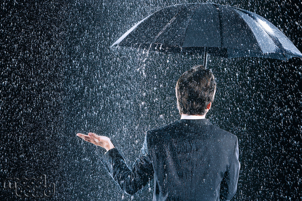 Businessman staying dry under umbrella during downpour back view