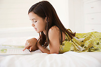 Girl reading story book lying on bed side view half length