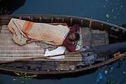 A man sleeps on a canoe on the Buriganga River in Dhaka, Bangladesh. The river acts as both a highway and a sewer, with 80 percent of the city's raw sewage draining into it from different parts of the city.