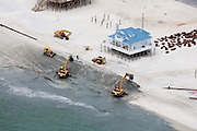 Heavy equipment is brought in to fortify the shallow shoreline and threatened property against rising seas and extreme weather.  A pipe (upper left) feeds in sand that is pumped from the bay to the equipment building up an artificial sand barrier.