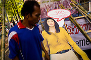 """11 MAY 2013 - BANGKOK, THAILAND:  A protesting farmer walks past a cardboard cutout of Thai Prime Minister Yingluck Shinawatra. Several hundred small scale family farmers camped out """"Government House"""" (the office of the Prime Minister) in Bangkok to Thai Prime Minister Yingluck Shinawatra to deliver on her promises to improve the situation of family farmers. The People's Movement for a Just Society (P-move) is a network organization which aims strengthen the voices of different, but related causes working to bring justice for marginalized groups in Thailand, including land rights for small-scale farmers, citizenship for stateless persons, fair compensation for communities forced to relocate to accommodate large scale state projects, and housing solutions for urban slum dwellers, among others.   PHOTO BY JACK KURTZ"""