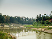 12 MARCH 2016 - LUANG PRABANG, LAOS: The bamboo foot bridge across the Nam Khan River near Luang Prabang. The bridge is seasonal. Villagers put it up every year, at the at the start of the dry season and take it down when the Nam Khan floods during the rainy season.  Laos is one of the poorest countries in Southeast Asia. Tourism and hydroelectric dams along the rivers that run through the country are driving the legal economy.     PHOTO BY JACK KURTZ