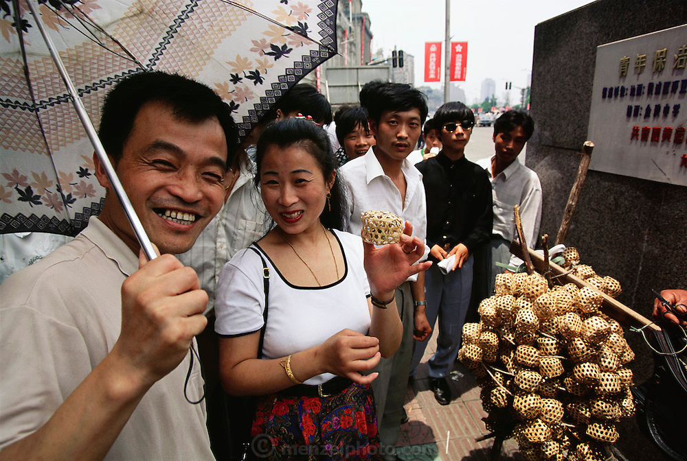 A couple shows off a singing cricket in a little cage that a vendor is selling on the Bund in Shanghai, China. The crickets are pets, not food. Image from the book project Man Eating Bugs: The Art and Science of Eating Insects.