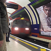Subway train entering underground station at Piccadilly Circus London England UK