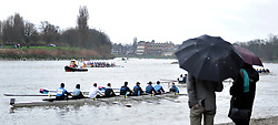 © Licensed to London News Pictures. 17/03/2012. London, UK. Acouple sheltering under umbrellas watch the race. Crews participate in the rain today,  Saturday 17th March, in The Head of the River Race which is rowed annually in March from Mortlake to Putney on the River Thames in London.  Over 400 crews of eights take part, making it one of the highest participation events in London.. Photo credit : Stephen SImpson/LNP