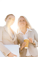 Young businesswomen with disposable cup and laptop looking away against sky