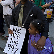African American father with his daughter, just few of the faces of the 99%  protesters.<br /> <br /> Occupy Wall Street movement, grassroots, nonviolent efforts of the  Occupy Wall Street movement , the 99% protesters in Foley Square in lower Manhattan before they march to  Zuccotti Park.<br /> <br /> This movements is about income equality and social justice issues.