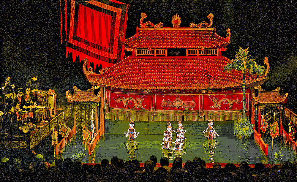 View of the performance in the Thang Long water puppet theater.  Audience heads, puppets in the water, backdrop, and orchestra on the left.