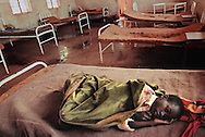 A young Rwandan refugee boy lies dying from complications brought on by Malaria.