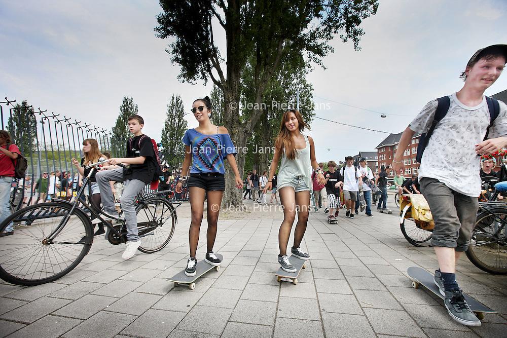 Nederland, Amsterdam , 5 juli 2012..AMSTERDAM -Stichting Kinetisch Noord(SKN)wilt datSkatepark Amsterdamvertrekt van het NSDM-werf in Amsterdam-Noord. De verhuurderwilt deloodsnamelijk hernieuwen en dus moet skatepark vertrekken. Skatepark Amsterdam is not amused en strijd met internet. Zo proberen de skaters het park te behouden...Al sinds twaalf jaar zit het Skatepark op het NSDM-werf. In december waren er gesprekken tussen het Skatepark en SKN. De Stichting bepaalde dat het huurcontract per 1 augustus eenzijdig wordt gestopt, tot verbazing van het Noord-Amsterdamse skatepark. SKN zal de loodsen namelijk hernieuwen metcommerciëlen partijen. Het park is niet blij met deze beslissing en voert nu groots actie door een skateparade dwars door de stad waar enkele hondenden skaters aan mee deden..Op de foto een rustpauze op het Olympiaplein..Foto:Jean-Pierre Jans