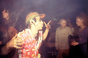 Raver dresssed in multi-coloured shirt and cap dancing at free party, Nottingham, U.K.