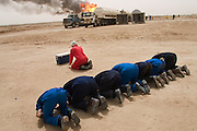 Firefighters from the Kuwait Oil Company (called KWWK: Kuwait Wild Well Killers) pray at noon by the first oil well fire they were working on in Iraq's Rumaila Oil Field. They did a double prayer at noon so they would not have to stop later in the day if they were at a critical phase. Later in the day they extinguished this smoky fire and the next day stopped the flow of gas and oil with drilling mud using what is called a stinger, a tapered pipe on the end of a long steel boom controlled by a bulldozer. Drilling mud, under high pressure, is pumped through the stinger into the well, stopping the flow of oil and gas. Many of the wells are 10,000 feet deep and produce huge volumes of oil and gas under tremendous pressure, which makes capping them very difficult and dangerous. Rumaila is also spelled Rumeilah.. (Supporting image from the project Hungry Planet: What the World Eats.)
