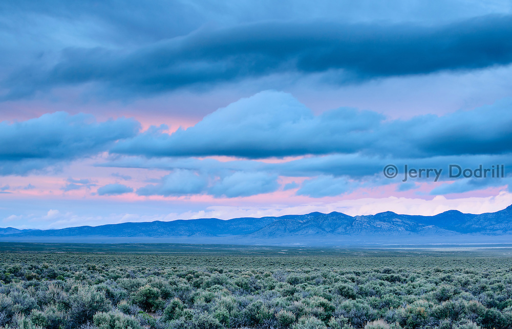 """Clouds glow to the East at twilight over the Great Basin's vast """"sagebrush ocean."""" Its easy to see why some call this region, typified by long narrow mountain ranges and vast valleys """"The Big Empty."""" The land here is managed by private ranchers, the BLM, and the Ely District of Toiyabe National Forest."""