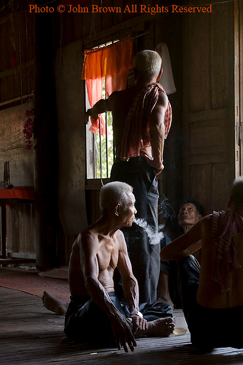 A group of poor elderly Khmer men are enjoying a conversation inside a wooden Buddhist temple in Ban Russei, Cambodia. Ban Russei is an agricultural area of Cambodia well known for its cultivation of tobacco products as well as a variety of food including fruit and vegetables. This unindustrialized rural area is home to Muslims and Buddhists alike.