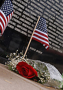 "Still covered with rain drops from an overnight thunderstorm a rose left by a visitor lies n front of  the Traveling Vietnam Veterans Memorial, the ""Traveling Wall"",  when it was Petoskey, Michigan this past week."