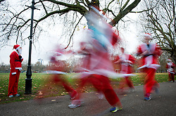 Runners dressed in Father Christmas costumes at the annual Santa Run in Battersea Park, London in aid of disability Snowsport UK , Saturday, 7th December 2013. Picture by Peter Kollanyi / i-Images