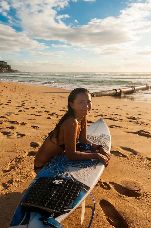 A female surfer takes a break on the beach, Manly Beach, Sydney, New South Wales, Australia