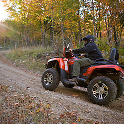 A man rides his ATV on through the forest at Jericho Mountain State Park in Berlin, New Hampshire.  White Mountains.