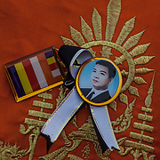 A Buddhist monk wear a memorial pin to former Cambodian King Norodom Sihanouk during funeral services Friday Feb. 1, 2013 in Phnom Penh, Cambodia.
