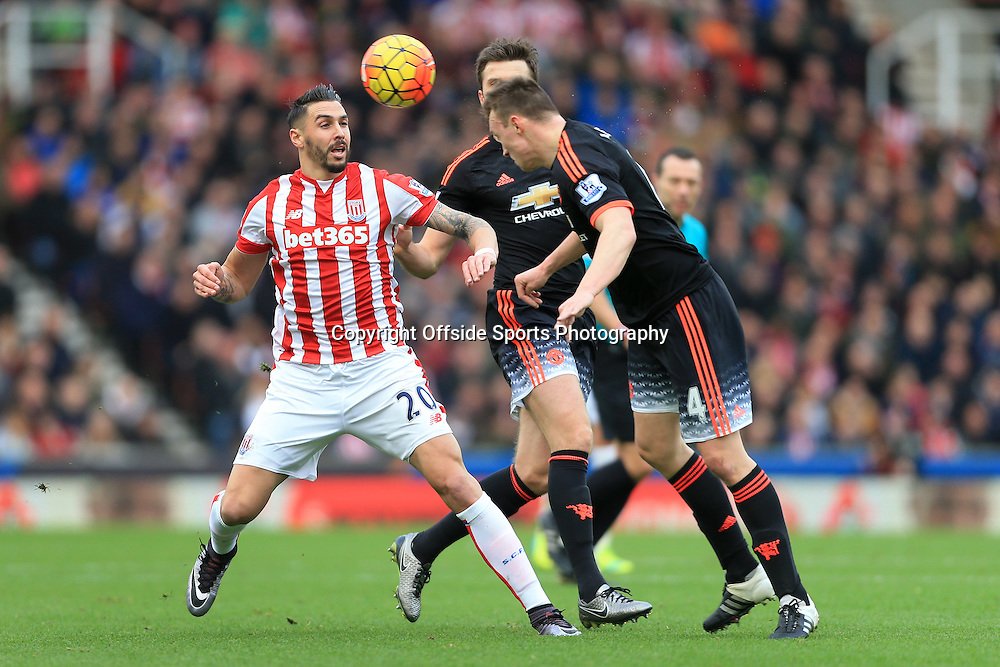 26th December 2015 - Barclays Premier League - Stoke City v Manchester United - Phil Jones of Man Utd clears with a header from Geoff Cameron of Stoke - Photo: Simon Stacpoole / Offside.