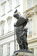pigeons on a Bronze statue of a man and young boy. Vienna, Austria