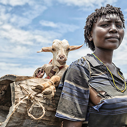 Portrait of a woman carrying a sheep on her shoulders, Omo Valley, Ethiopia, Africa
