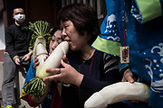 People hold radish sculpture of giant phallus and pose for the cameras during the Kanamara Festival at Kawasaki on April 2, 2017. The Kanamara Matsuri or the festival of the Steel Phallus is held on the first Sunday in April at the Kanayama shrine. The festival started by prostitutes who wished to pray for protection from sexually transmitted diseases, and now for easy delivery, marriage and married-couple harmony. It become a tourist attraction and is used to rise money for HIV disease. 02/04/2017-Kawasaki, JAPAN